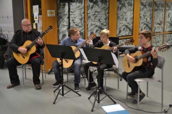 pojat soittavat kitaraa opettajan kanssa