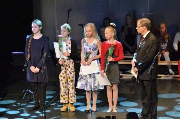 Pekka Hynninen jakamassa ruusuja oppilaille