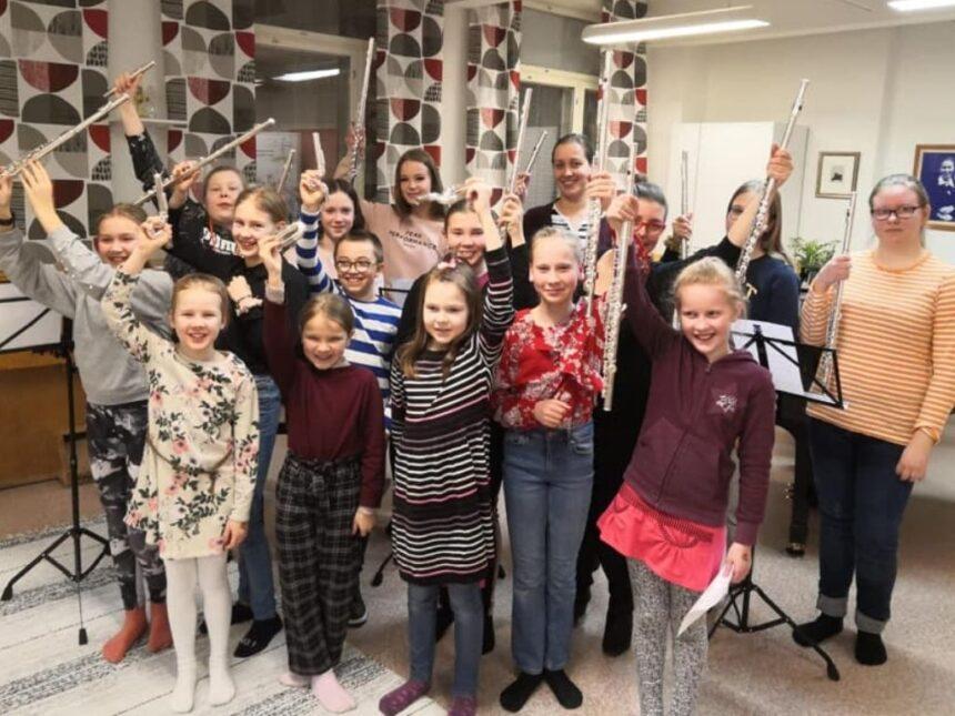 hymyileviä huilun soiton opiskelijoita huilut kädessään