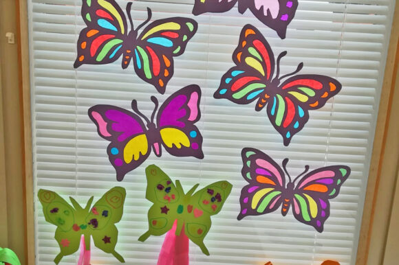 paljon värikkäitä askarreltuja perhosia ikkunassa