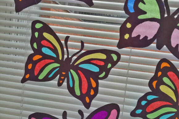 värikkäitä silkkipaperiperhosia ikkunassa
