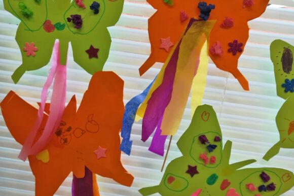 värikkäitä paperista arkarreltuja perhosia ikkunassa