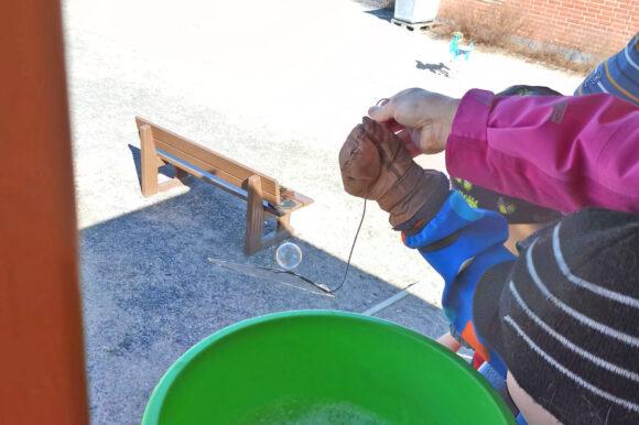 lapset tekemässä saippuakuplia